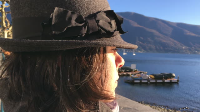 vídeos y material grabado en eventos de stock de woman with hat sitting on a bench and enjoy the view over alpine lake with mountain and sunlight - sobretodo