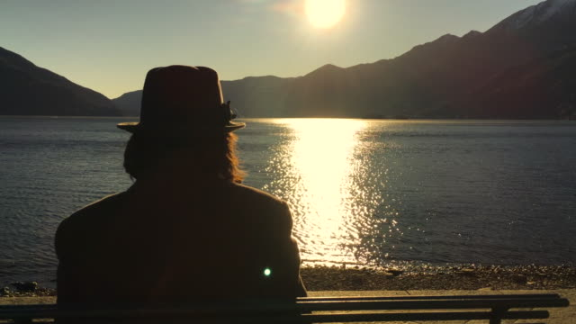 woman with hat sitting on a bench and enjoy the view over alpine lake with reflection and mountain with sunlight - オーバーコート点の映像素材/bロール
