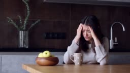 Woman with headache sitting in kitchen