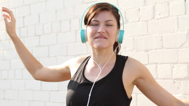 vídeos de stock, filmes e b-roll de woman with headphones dancing joyfully - cabeça para trás