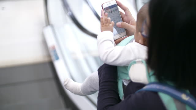 SLO MO Woman with her baby using mobile in shopping mall