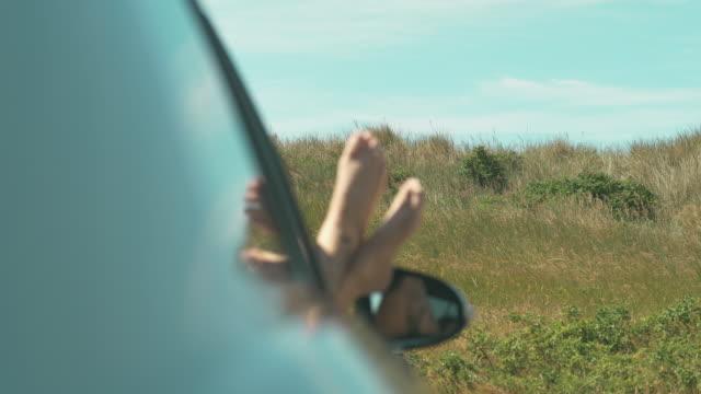 stockvideo's en b-roll-footage met vrouw met haar voeten omhoog in de autoruit - autoreis