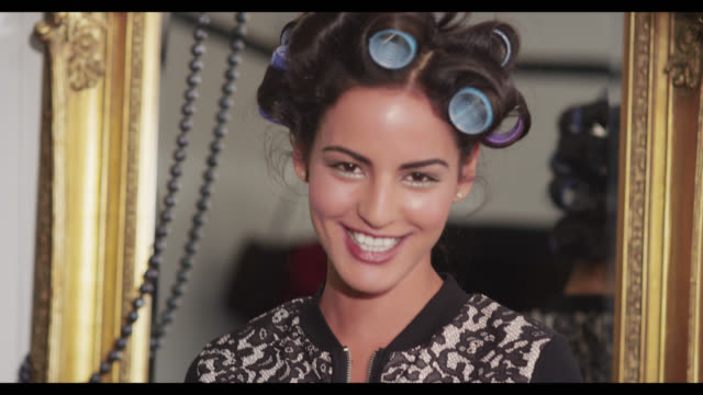 A woman with her hair in rollers blows a kiss to camera