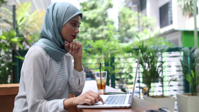 vídeos de stock, filmes e b-roll de mulher com hijab trabalhando no café - vestuário modesto