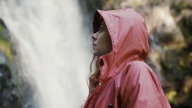 woman with hooded rain jacket by waterfall - レインコート点の映像素材/bロール
