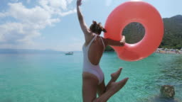 MS Woman with inflatable ring jumping into sunny ocean,Peljesac,Croatia