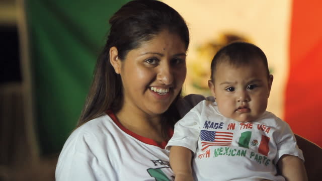 vídeos y material grabado en eventos de stock de ms slo mo woman with kid (6-11 months), wearing mexican and american flag shirts / homestead, florida, usa - inmigrante