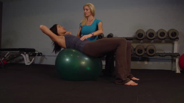 """""""ms pan woman with lady trainer doing exercise of ab crunches on yoga ball / beverly hills, california, united states"""" - bodyweight training stock videos & royalty-free footage"""