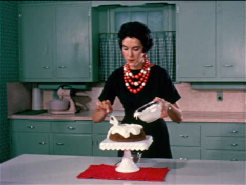 1950 woman with large necklace spooning white icing onto cake / industrial - 1950 stock videos & royalty-free footage