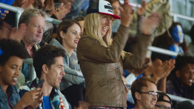 woman with long blonde hair and a baseball cap cheering amongst other sports fans on the stadium tribune - 前ボケ点の映像素材/bロール