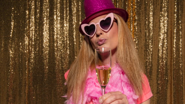 woman with long blonde hair taking photos in the photo booth using funny props - sunglasses stock videos & royalty-free footage
