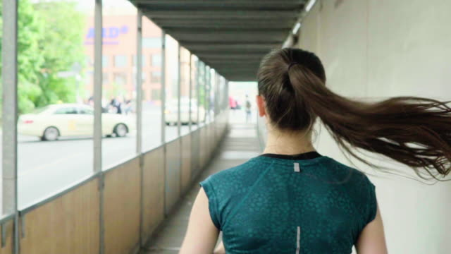woman with long hair jogging on covered sidewalk in city - ponytail stock videos & royalty-free footage