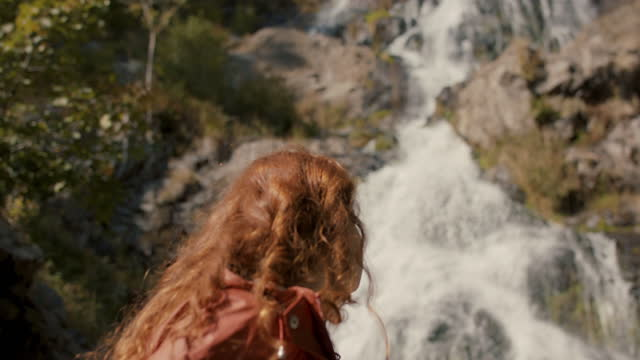 woman with long red hair by waterfall - introspection stock videos & royalty-free footage