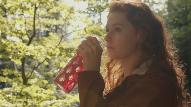 woman with long red hair drinking from reusable bottle in forest - ウォーターボトル点の映像素材/bロール
