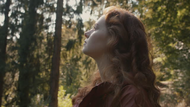 woman with long red hair enjoying sunshine in forest - inhaling stock-videos und b-roll-filmmaterial