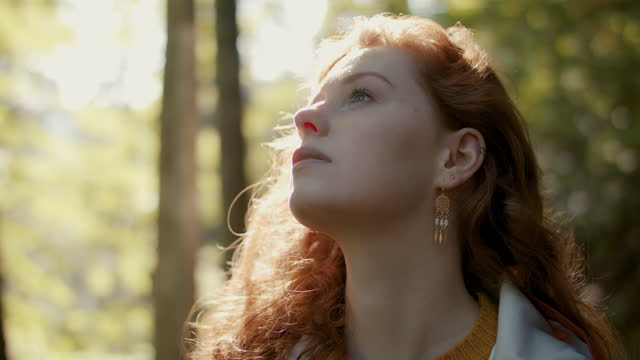 woman with long red hair in sun in forest looking up - beautiful woman stock videos & royalty-free footage