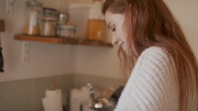 woman with long red hair making tea in kitchen smiling - ティーポット点の映像素材/bロール