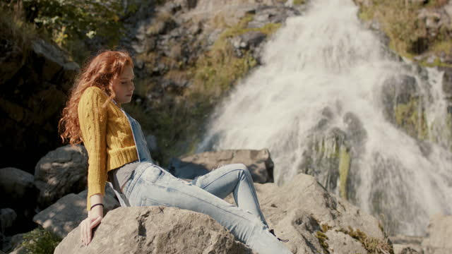 woman with long red hair sitting by waterfall - spring flowing water stock-videos und b-roll-filmmaterial