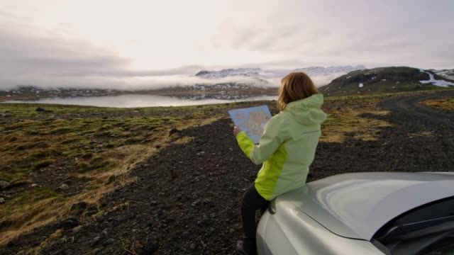 vídeos de stock e filmes b-roll de ws woman with map standing at car overlooking remote landscape,iceland - remote location
