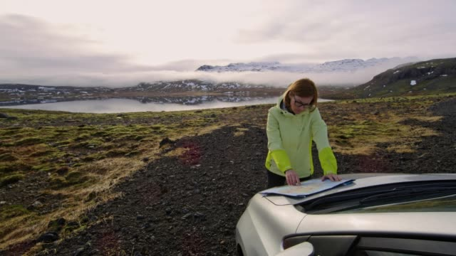 vídeos de stock e filmes b-roll de ws woman with map standing outside car overlooking remote landscape,iceland - remote location