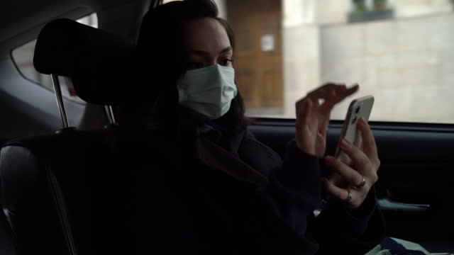 woman with mask is using smart phone at the back seat of the car during journey. - passenger seat stock videos & royalty-free footage
