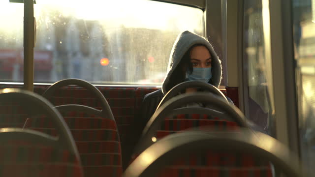 woman with mask traveling alone by public bus in london. - bus stock videos & royalty-free footage