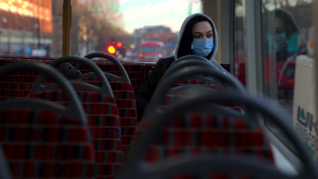 woman with mask traveling alone by public bus in london - cinematography stock videos & royalty-free footage