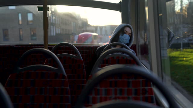 woman with mask traveling alone by public bus in london. - cinematography stock videos & royalty-free footage