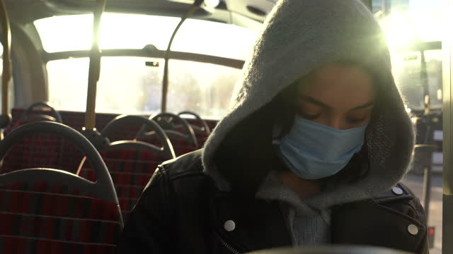 woman with mask traveling alone by public bus - cinematography stock videos & royalty-free footage