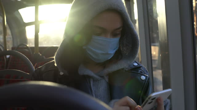 woman with mask using smart phone on public bus - cinematography stock videos & royalty-free footage