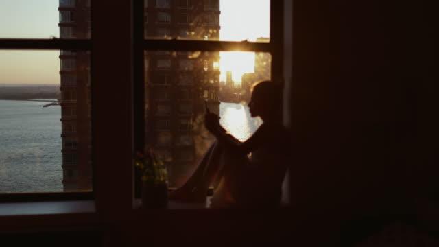vidéos et rushes de femme avec le téléphone portable par la fenêtre à new york - fenêtre