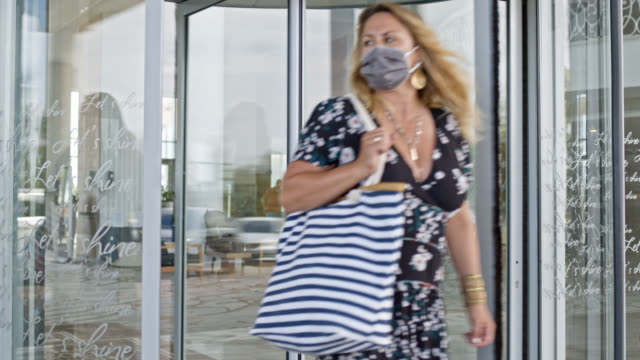 woman with mouth nose protection mask and shoulder bag leaves business hotel building - shoulder bag stock videos & royalty-free footage