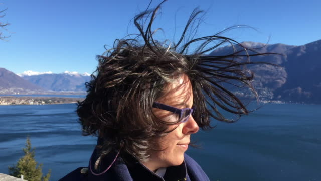 Woman with Moving Hair and Eyeglasses in a Windy Day