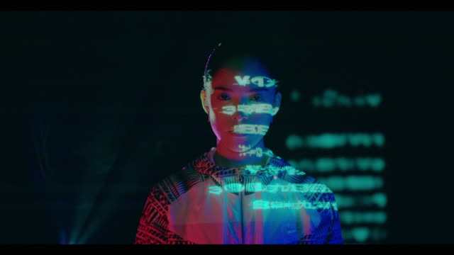 vidéos et rushes de woman with numbers and symbols projected on her - technologie