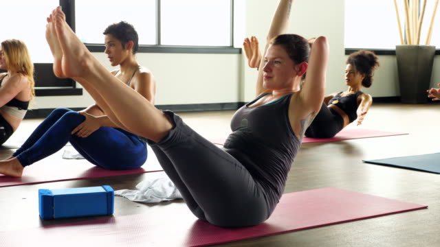 MS Woman with one arm in boat pose during hot yoga class in exercise studio