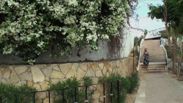 woman with pareo descending staircase by white bougainvillea flowers - sarong stock videos and b-roll footage