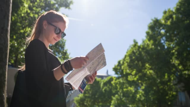 Woman with Paris city map admiring national landmarks