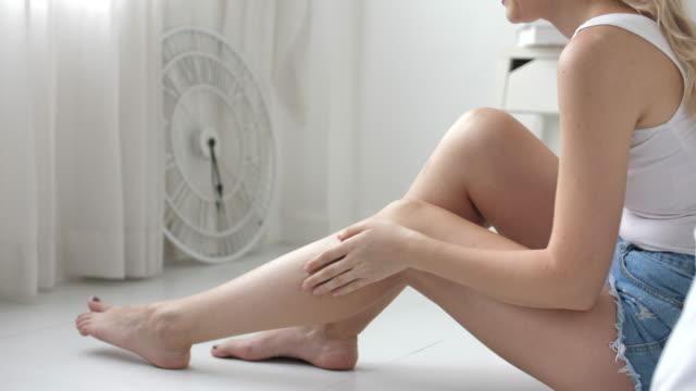 vídeos de stock, filmes e b-roll de mulher com corpo perfeito que aplica a loção de refrescamento do creme ou do corpo em seus pés - moisturiser