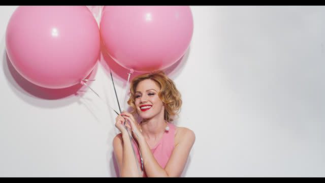 A woman with pink balloons