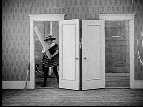 1924 b/w ws woman (louise carver) with plank chasing man (charles murray) around and through doors, he hides and she hits doors with plank, then man hits woman with plank / usa - spanking stock videos and b-roll footage