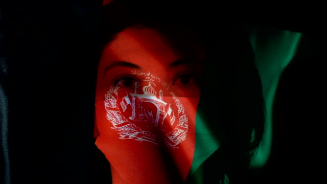woman with protective face mask on afghanistan flag. protection for viruses and infections. - afghanistan stock videos & royalty-free footage