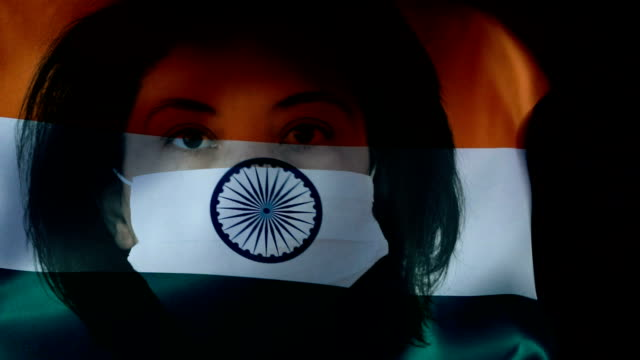woman with protective face mask on indian flag. protection for viruses and infections. - prevenzione delle malattie video stock e b–roll