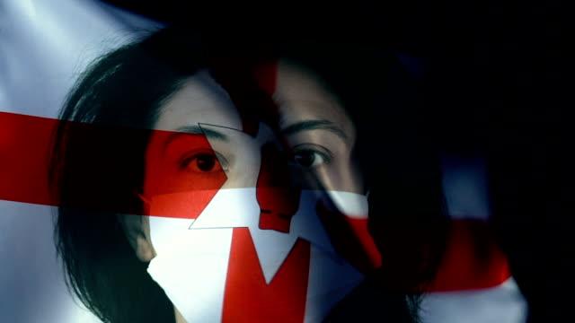 北アイルランドの旗に保護フェイスマスクを持つ女性。ウイルスおよび感染症の保護。 - ベルファスト点の映像素材/bロール