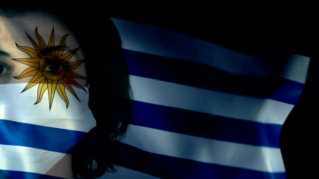 woman with protective face mask on uruguaian flag. protection for viruses and infections. - uruguaian flag stock videos & royalty-free footage
