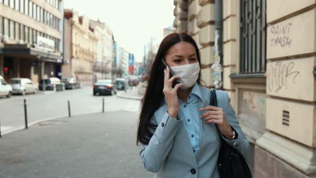 woman with protective mask on city street - high street stock videos & royalty-free footage