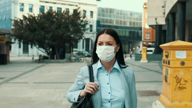 woman with protective mask on city street - young women video stock e b–roll