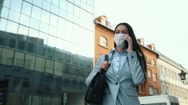 woman with protective mask on city street - communication stock videos & royalty-free footage