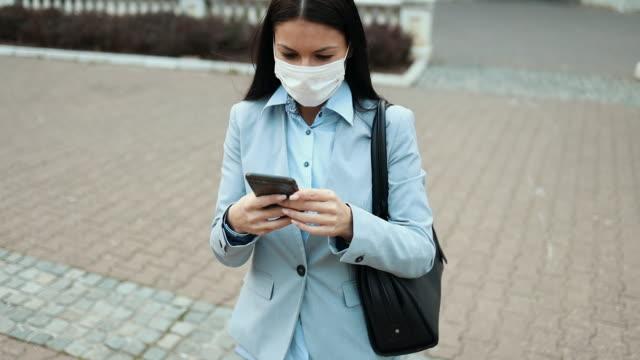 vídeos de stock, filmes e b-roll de mulher com máscara de proteção na rua da cidade - obscured face