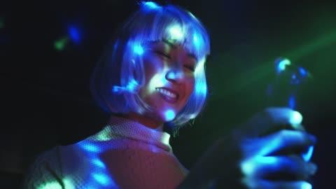 vídeos y material grabado en eventos de stock de cu woman with purple hair in a club at night - letrero de neón