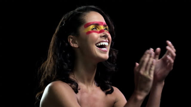 Woman with red and yellow face paint clapping
